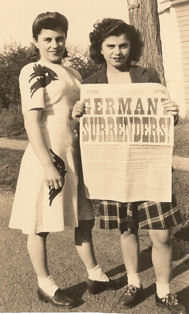 My mom and her sister Eva holding the paper announcing the end of the war.